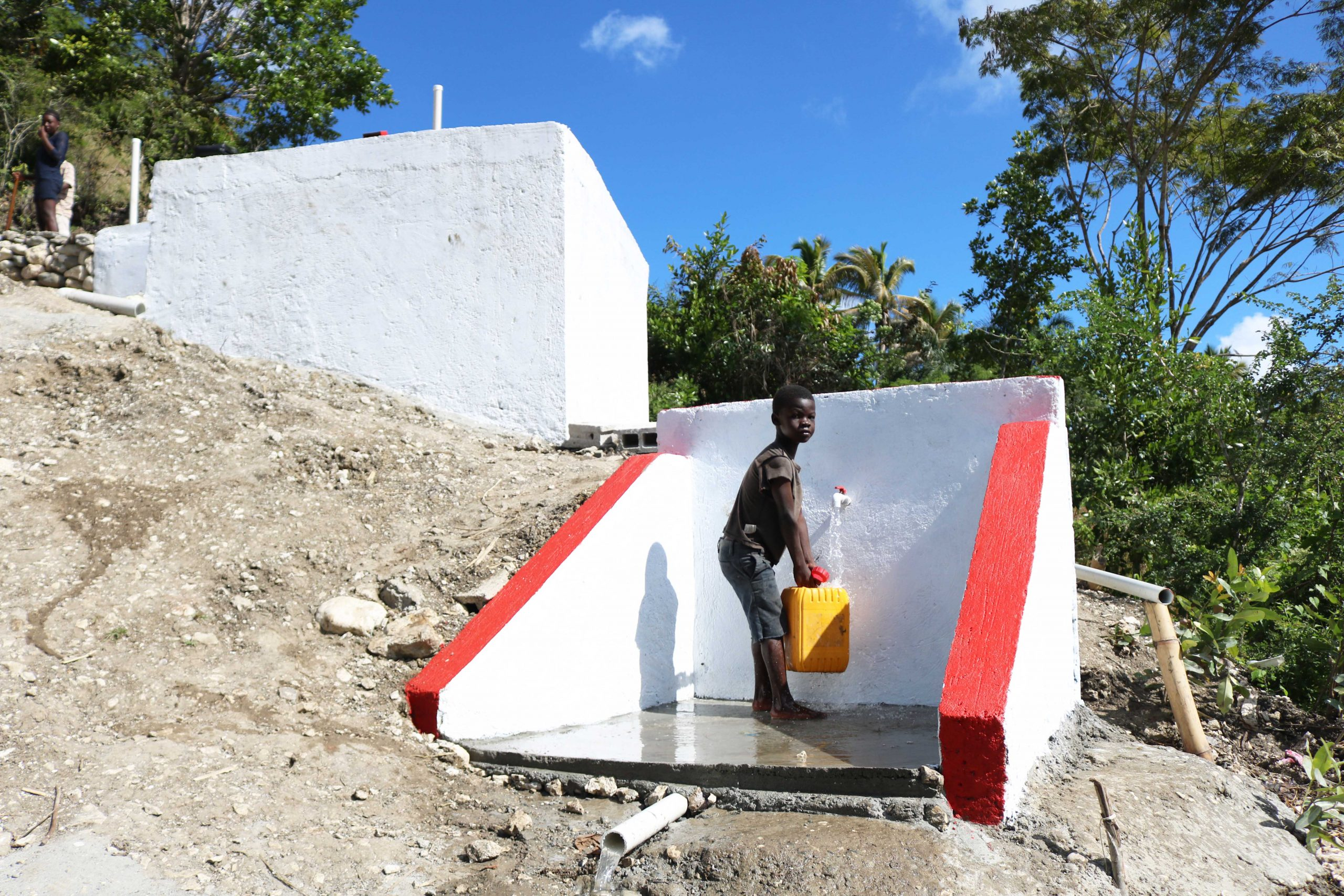 A child using a newly constructed water point. Trees were planted upstream of the water source to improve rainwater infiltration in the soil (Osse Manuel Recule, Haiti Red Cross)